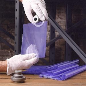 A man placing a metal part in a transparent purple colour VCI Biodegradable Bags